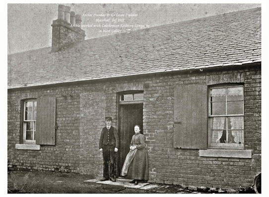 Photo:Archibald Dundas and his wife, great grandparents of Mrs Meg Stenhouse.  Standing outside their house at Muirhall, before 1911.  Archie worked with the Caledonian Railway Company in West Calder.
