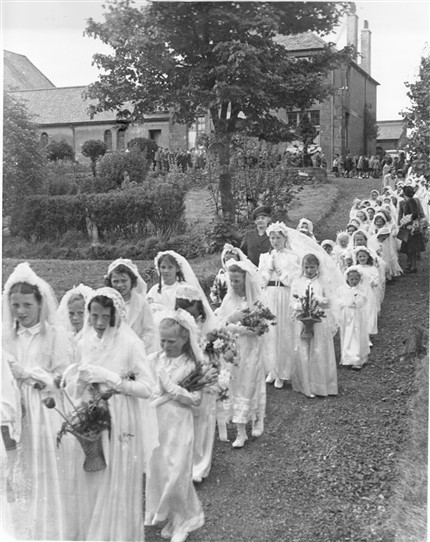 Photo:First communicants.  In the background the chapel (left), and Presbytery [the priest's house] (right).